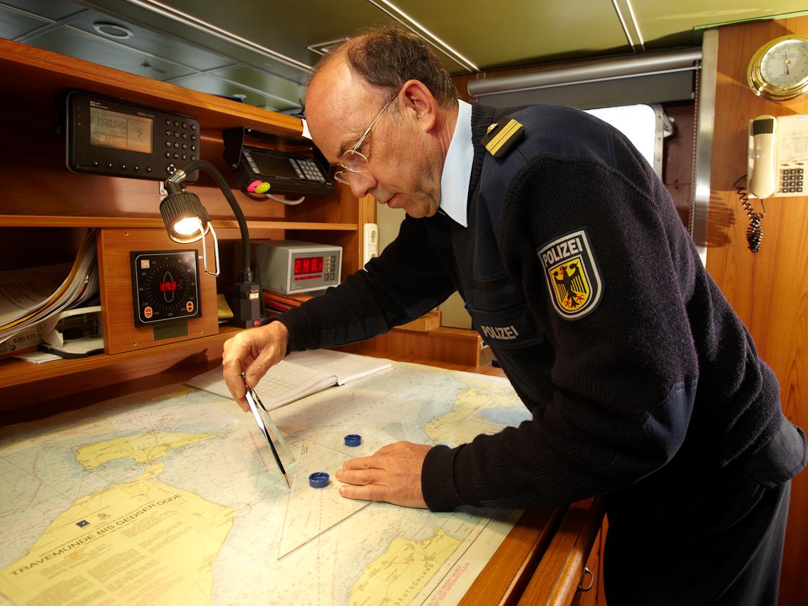 Neustadt in Holstein, Lübecker Bucht, Ostsee. 7.5.2010 Küstenwache im Einsatz auf der Ostsee. Die Bundespolizei ist ein Teil der deutschen Küstenwache. Das Wachboot NEUSTRELITZ der Bundespolizei lauft bei schlechtem Wetter und Windstarke 8 zu einer Routinefahrt in die Lübecker Bucht aus. Schon nach wenigen Minuten sichtet die Mannschaft ein unbemannt im Wasser treibendes Surfbrett. Kommandant Peter Gau koordiniert von der Brücke aus eine Suchaktion nach dem vermissten Surfer. Er zeichnet die Position des aufgefundenen Surfbretts in die Seekarte ein und berechnet anhand von Wind und Wasserströmung das Gebiet, in dem nach der vermissten Person gesucht werden muss.