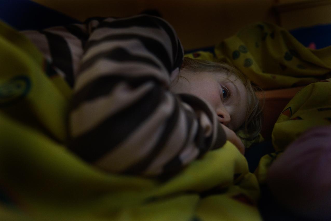 """Die 5 jährige Leny-Marie halt in der Kindertagesstatte """" Arche Noah """" im Stadtteil Sachsenhausen in Frankfurt am Main am Freitag, 07.05.2010 im Schlafraum mit anderen Gruppenkindern die tägliche Mittagspause. Sie lauscht einer Vorlese CD. Leny findet diese Pause eigentlich doof, denn man könne doch viel besser draußen spielen zu dieser Zeit oder mit den anderen alteren Kindern Quatsch machen, aber andererseits dürfen die Älteren während der Mittagspause ja die Vorlesegeschichte hören; das sei dann auch ok..."""