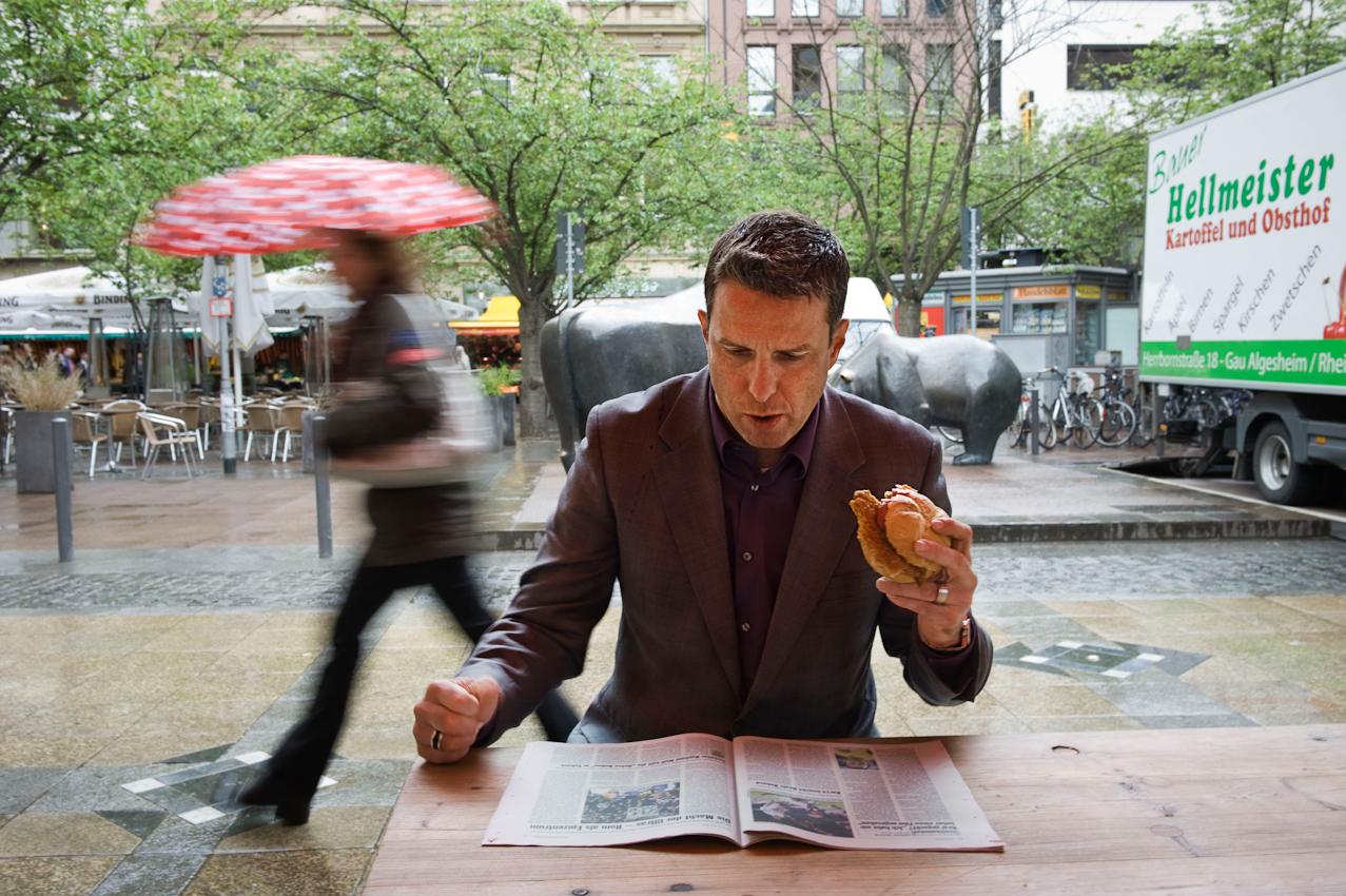 """Oliver Roth, Chefbörsenhandler bei der Close Brothers Seydler Bank an der Frankfurter Börse macht eine kurze Mittagspause an einem Wurststand auf dem Börsenplatz in der Innenstadt von Frankfurt am Main am Freitag, 07.05.2010. Freitags ist Bauernmarkt vor der Börse und wie jeden Freitag freut sich Herr Roth auf """"sein Schnitzelbrötchen """" und einen kurzen Blick in das Kicker Fußballmagazin. So eine Pause dauert bei Herrn Roth selten länger als 15 Minuten. Oliver Roth ist ehemaliger Fussballprofi aus der 1. Fußball Bundesliga, und hat u.a. bei Borussia Dortmund gespielt."""