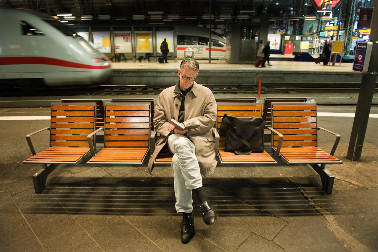 Oliver Reese, Intendant am Schauspiel Frankfurt, liest ein Buch am Hauptbahnhof von Frankfurt am Main am späteren Freitag Abend, 07.05.2010. Bahnhöfe sind mit die einzigen Orte fur Herrn Reese, an denen er ungestört lesen, denken und schreiben kann und dies auch gern dort praktiziert. Pause vom Alltag im Theater.