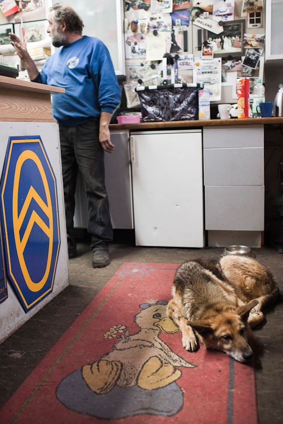 Das Foto entstand in dem Empfangsbuero der Auto-Werkstatt Franz Schreier 2CV Service+Teile in 74889 Sinsheim-Reihen, Baden-Wuerttemberg, Deutschland am 7. Mai 2010 um 19.54 Uhr. Zu sehen ist der Chef Franz Schreier im Gespraech, im Vordergrund liegt sein alter Hund Shorty.