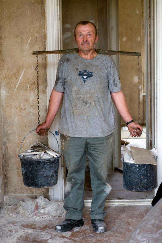 Eine Altbauwohnung in Berlin-Kreuzberg wird restauriert. Der Steinträger trägt mit seiner 60 Jahre alten Trage den Schutt aus dem sechsten Stock aus dem Haus raus.