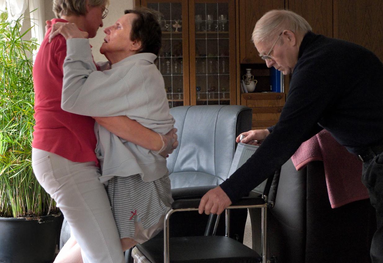 Ein Tag Deutschland, 07.05.2010, 59329 Wadersloh, NRW: 80 jähriger Mann pflegt seine an Multisystematrophie (MSA) erkrankte palliative 77 jährige Frau zu Hause.  Die Pflegeschwester hilft beim umsetzen in den Transportstuhl.