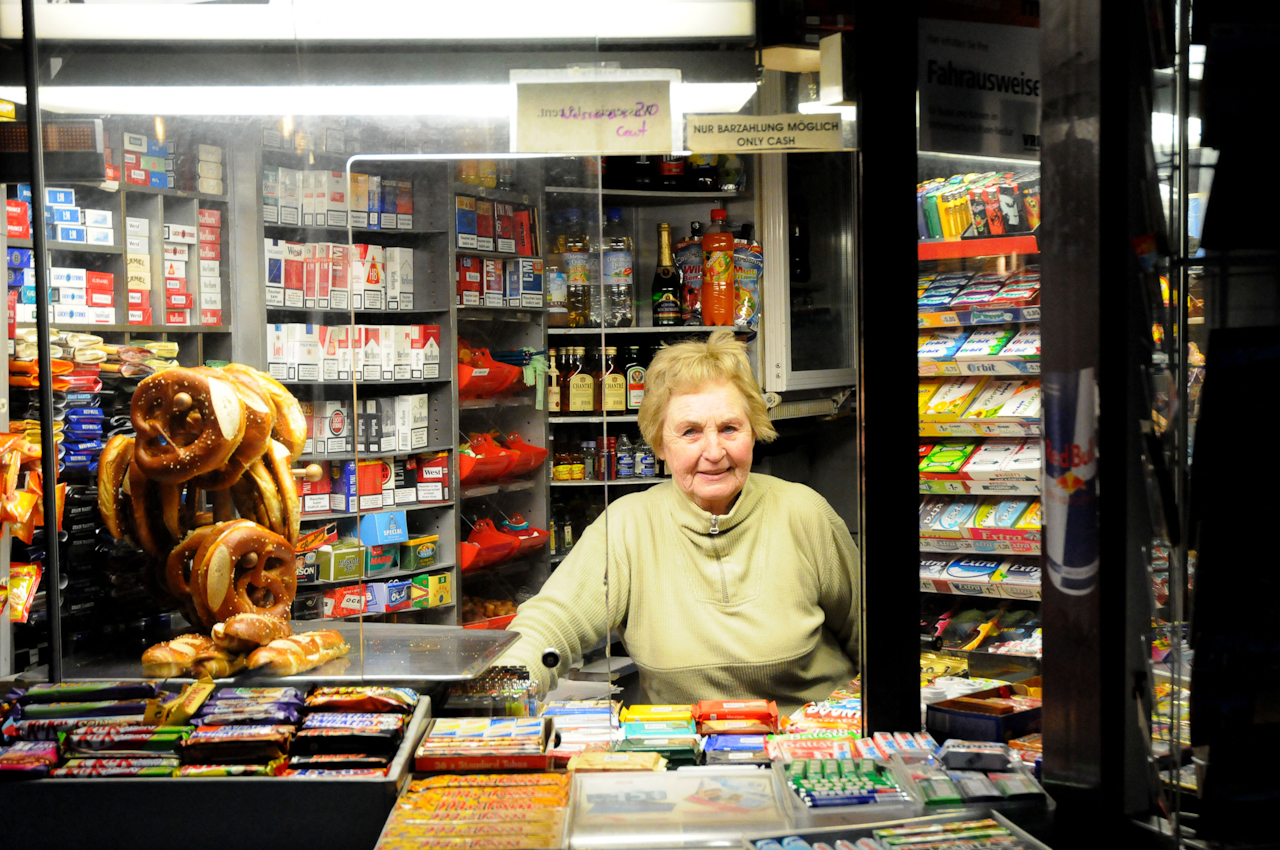 Heidelberg, Bismarckplatz am frühen Morgen. Der Kiosk öffnet. Gerda Thome richtet Butterbrezel