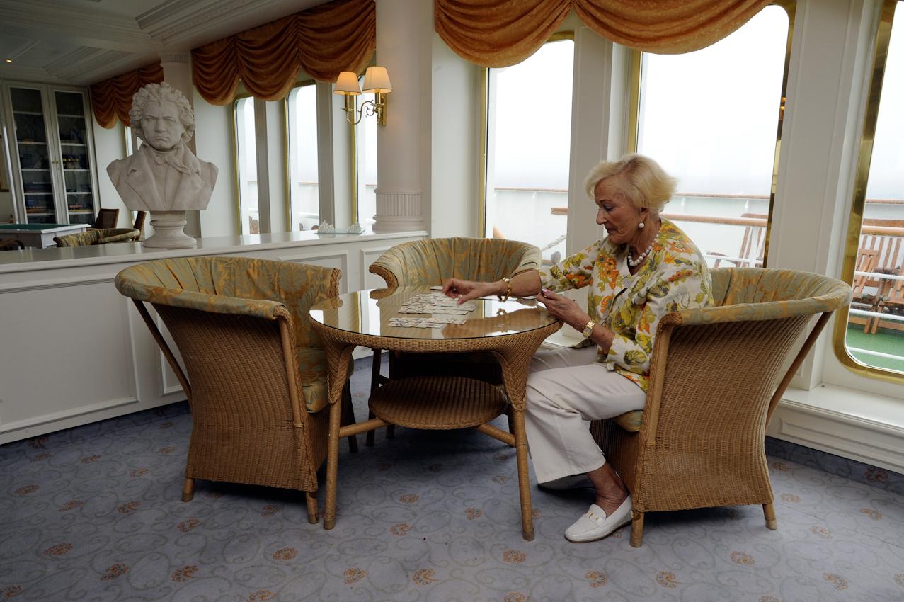 Auf dem Kreuzfahrtschiff MS Deutschland. Ältere Dame legt sich die Karten auf der Lido-Terasse.