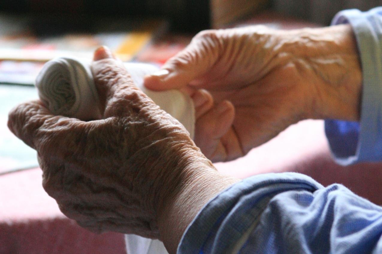 Die 86-jährige Hedwig Hansen sitzt im Wohnzimmer ihres Hauses in Tönnig und wickelt die Bandagen auf, mit denen sie in der Nacht ihre Knöchel umwickelt hatte.