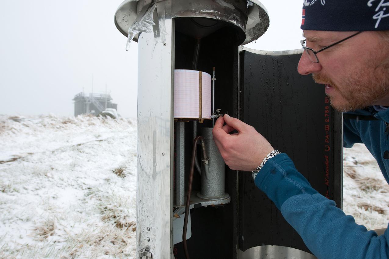 Wo kommt das Wetter her? - Ein Tag mit dem Wetterdiensttechniker Rene Sosna auf dem Brocken.  Rene Sosna bei der Kontrolle und erneuten Eichung am Regenschreiber. Der Regenschreiber hält den Niederschlagsverlauf an einer Station fest. Er ist eine von vielen Messstationen im Messfeld der Wetterwarte auf dem Brockenplateau.