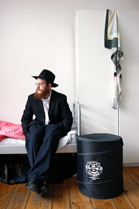 Nach dem Frühstück plant Jehoshua Berkovicz den weiteren Tag. Er sitz in seinem Zimmer in der WG auf dem Bett und überlegt, welcher Aufgabe er sich zuerst widmet.