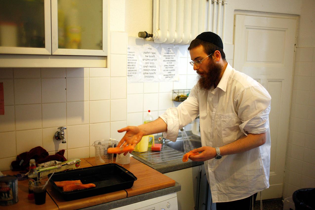 """""""In der Yeschiwa lernt man das Kochen!"""" sagt Jehoshua Berkovicz. Nach der Erfüllung der Pflichten des Tages bereitet er gemeinsam mit den anderen Studenten der Yeschiwa in der Küche der Wohngemeinschaft das gemeinsame Schabbatmahl vor. Dabei ist es wichtig, dass alles pünktlich zum Beginn des Schabbats fertig ist, da am Schabbat keine Arbeit verrichtet werden darf. Kochen ist leider auch Arbeit. Der Lachs wird nach dem Waschen von Jehoshua mariniert."""