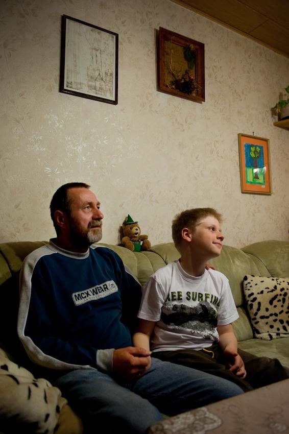 Jan Phillip mit seinem Opa im Wohnzimmer der Großeltern. Der Opa ist derzeit fur ihn die wichtigste Bezugsperson. -- Jan Phillip Biesecke (10 Jahre), der bei seinen Großeltern in Brandenburg/Havel lebt, geht jeden Tag nach der Schule in eine Tagesbetreuungsgruppe. Dort bekommt er Nachhilfe und verbringt mit anderen Kindern den Nachmittag. Jan Phillips Mutter hatte ihn mit 3 Jahren verlassen. Sein Vater, mit der Situation völlig überfordert, hatte ihn zu den Großeltern gegeben, bei denen er jetzt immer noch lebt. Die Tagesbetreuung wird vom Jugendamt finanziert und ist für Jan Phillips Großeltern eine Möglichkeit sich bei der Erziehung, die sie nur zum Teil leisten können, helfen zu lassen.