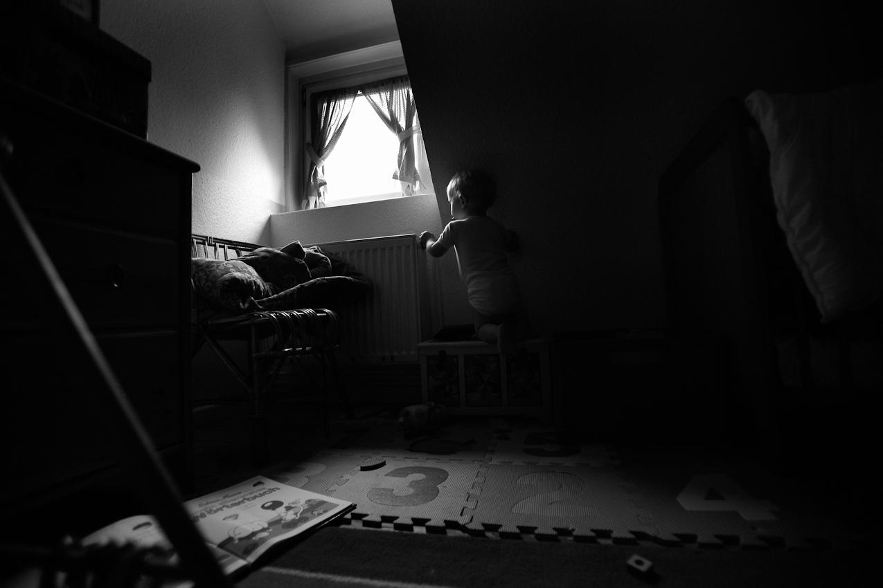 Elias klettert auf seine Spielkiste, um am Radchen der Zentralheizung drehen zu können. ----- Titel:  Ganz bei sich -- Ein Tag im Leben von Elias Valentin Morascher; Sohn des Fotografen Arnold Morascher. Mein Hauptinteresse bestand darin, das Kind nicht in Interaktion mit anderen sondern in Konzentration auf sich selbst zu fotografieren. Die Serie zeigt die Eigenständigkeit des 18 Monate alten Kindes (geboren 14.11.2008),  die konzentrierten Momente. Lernen, Erfahren, Bewegung, selbständiges Spielen; auch die Frustration des Kindes, als es z.B. nicht in der Lage ist, alleine auf das Bett der Eltern zu klettern. Die Serie entstand in etwa vier Stunden zwischen 13:00 und 17:00 Uhr am 07.05.2010 und zeigt ein Stück Leben eines Kleinkindes in Deutschland /22175 Hamburg/Bramfeld.