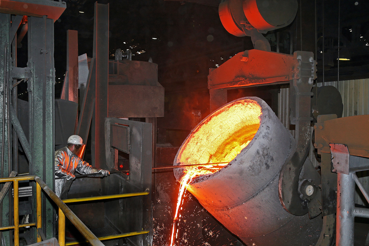 Der Giessereimeister schoepft aus der Pfanne mit dem fertigen 30 Tonnen Roheisen, Schlackereste und eventuell verunreinigtes Eisen von der Oberflaeche ab bevor es zur Veredelung mit Magnesium geht.  Das Verfahren in dieser Eisengiesserei wird seit ca. 160 Jahren fast unveraendert fortgefuehrt. Noch heute ist diese Eisengiesserei ein Unternehmen mit kontinuierlichem Absatz. Die Eisengussprodukte dienen meist als Gehaeuse fuer grosse Turbinenanlagen, Kokillen oder Gehaeuse von Schiffsmotoren. Eisenguss in der Eisengiesserei der Friedrich - Wilhelms- Huette in Muelheim / Ruhr