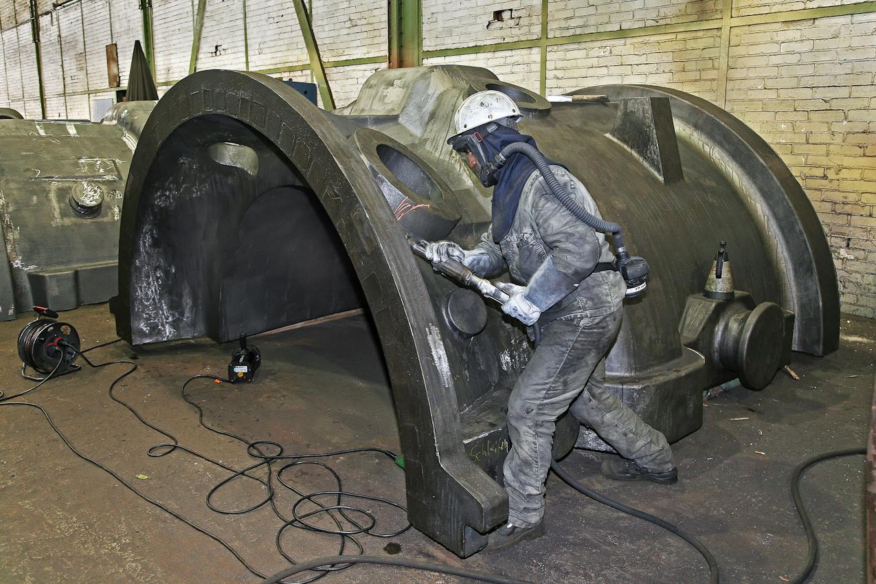 Das fast fertige Pumpengehaeuse wird einem letzten Schliff in der Versandhalle unterzogen. Ueberschuessige Grate und Unebenheiten werden entfernt. Der tuerkische Arbeiter Murat Guelen muss unter einer beatmeten Vollmaske Schwerstarbeit verrichten. Das Verfahren in dieser Eisengiesserei wird seit ca. 160 Jahren fast unveraendert fortgefuehrt. Noch heute ist diese Eisengiesserei ein Unternehmen mit kontinuierlichem Absatz. Die Eisengussprodukte dienen meist als Gehaeuse fuer grosse Turbinenanlagen, Kokillen oder Gehaeuse von Schiffsmotoren. Eisenguss in der Eisengiesserei der Friedrich - Wilhelms- Huette in Muelheim / Ruhr