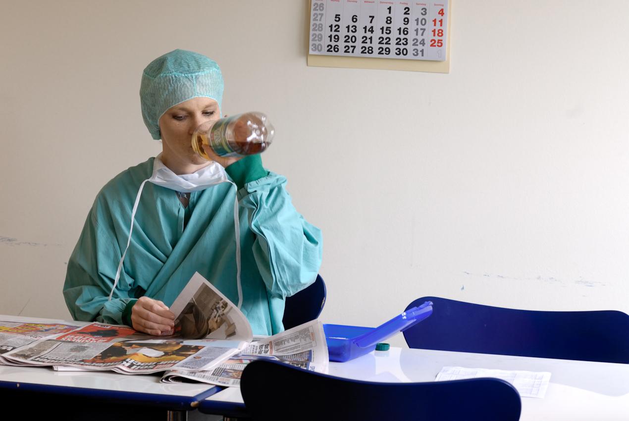 Gemeinschaftsraum für das OP-Personal in Nähe der Operationssäle. Eine der OP-Schwestern macht zwischen den Operationen kurz Pause, trinkt Ginger Ale und liest in der Zeitung.