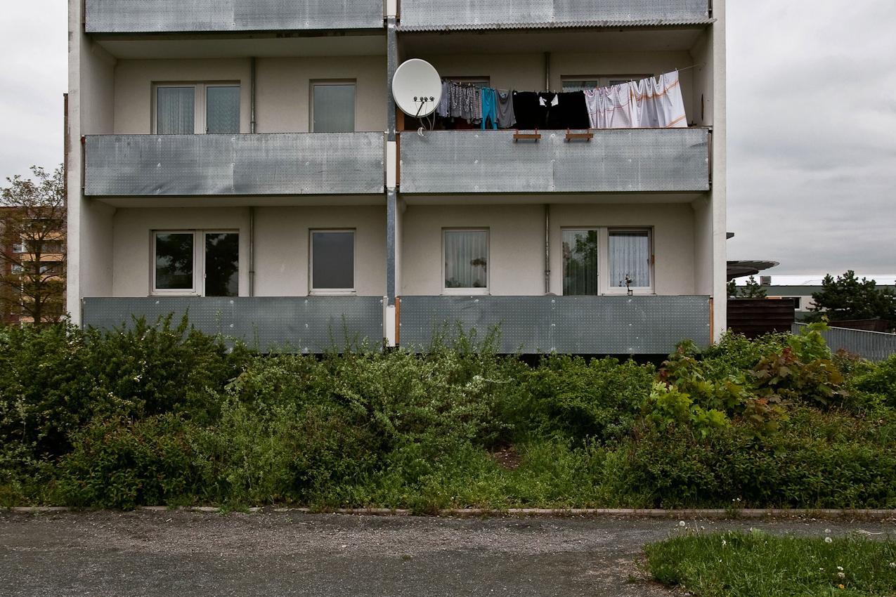 """Kopfseite eines Wohnblocks mit Balkonen an der """"Neuen Mitte"""" in der Grunstraße."""
