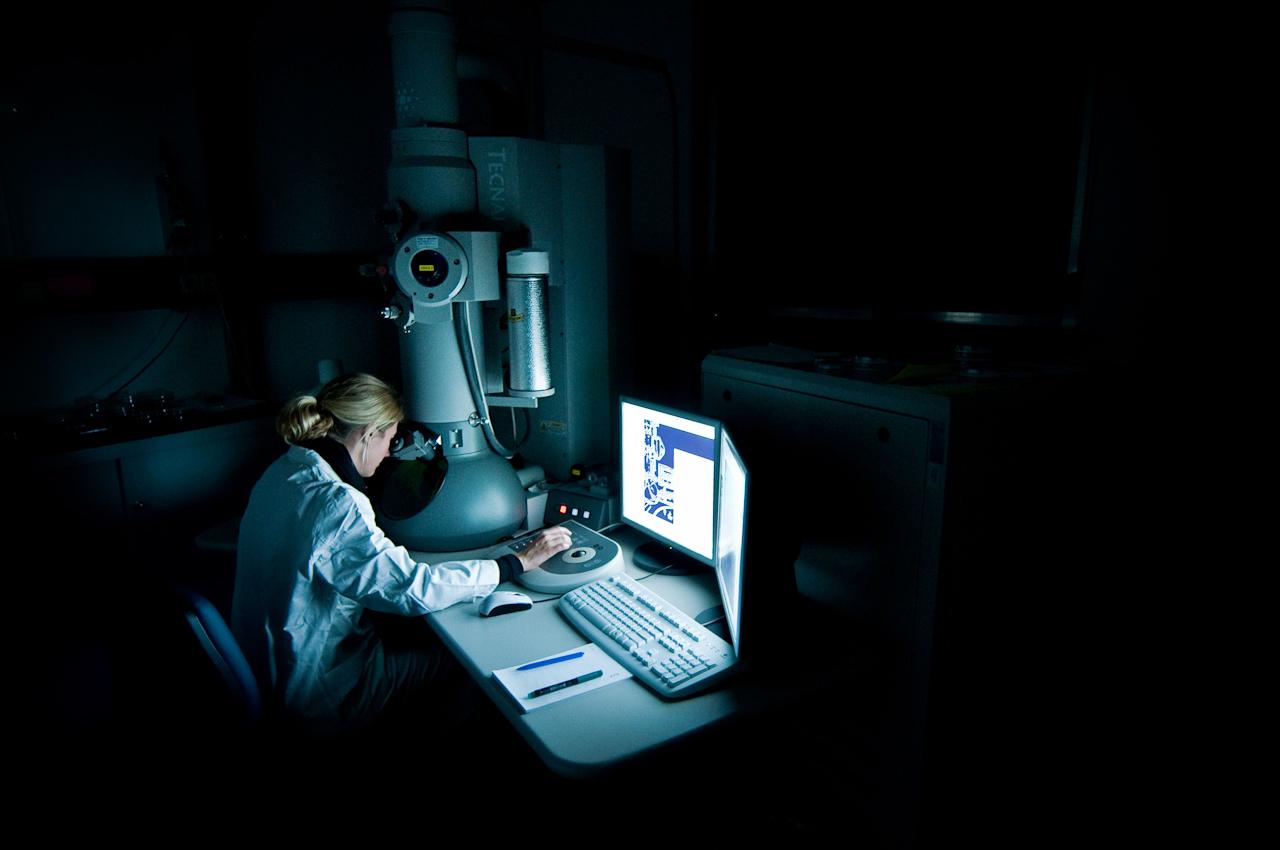 Eine Forscherin an einem Elektronenmikroskop.