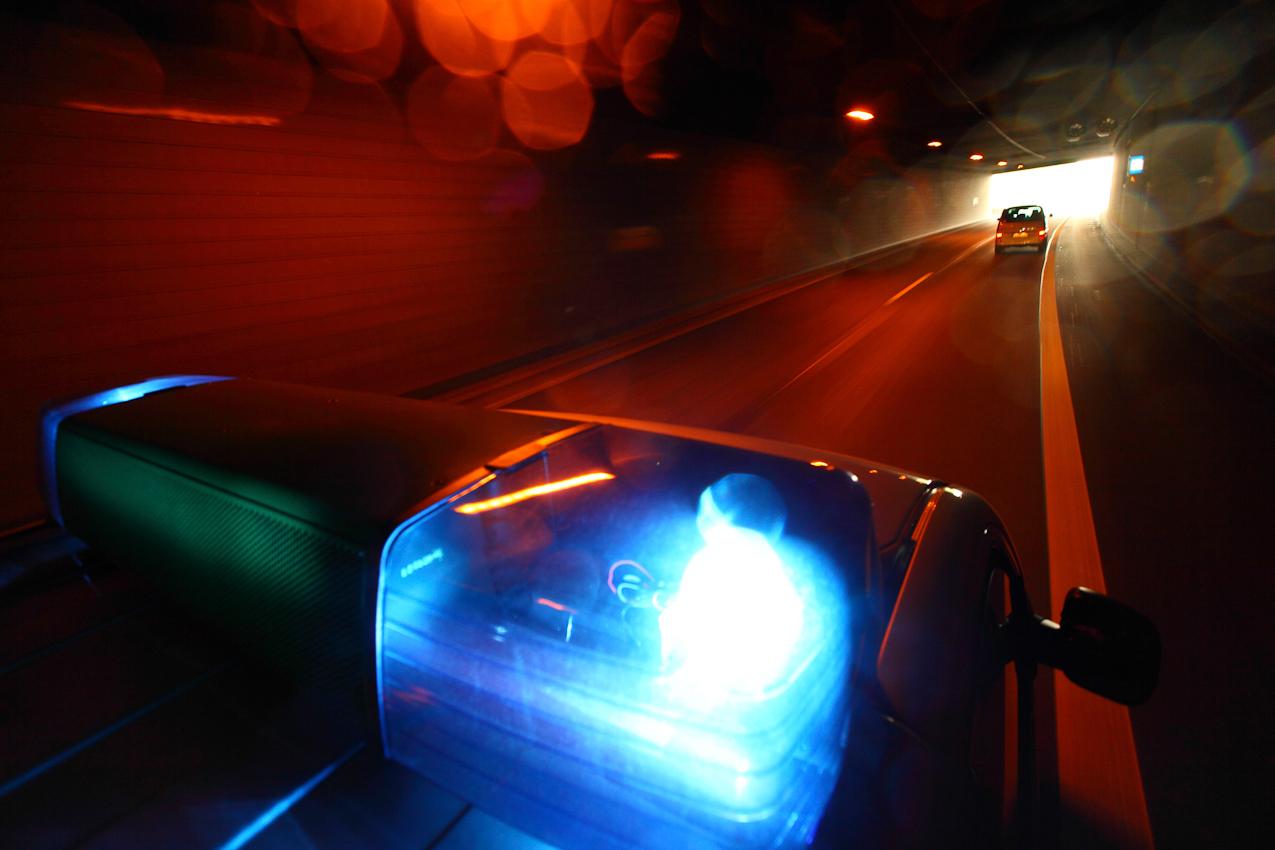 Ein Tag Deutschland, auf der Autobahn A40, Ruhrschnellweg. Einsatzfahrt der Autobahnpolizei. Zu einer Stauabsicherung bei Duisburg. Mit Blaulicht durch den Ruhrschnellwegtunnel. Noch ist die Bahn frei. Am Kreuz Kaiserberg stauen sich die Fahrzeuge bei der Auffahrt zur A3 Richtung Köln. Stauende in der Kurve, typische Unfallquelle. Doch der Streifenwagen kommt gut durch, der Berufsverkehr mit seinen alltaeglichen Staus ist vorbei, pausiert bis zum Nachmittag. Essen, NRW, Deutschland.