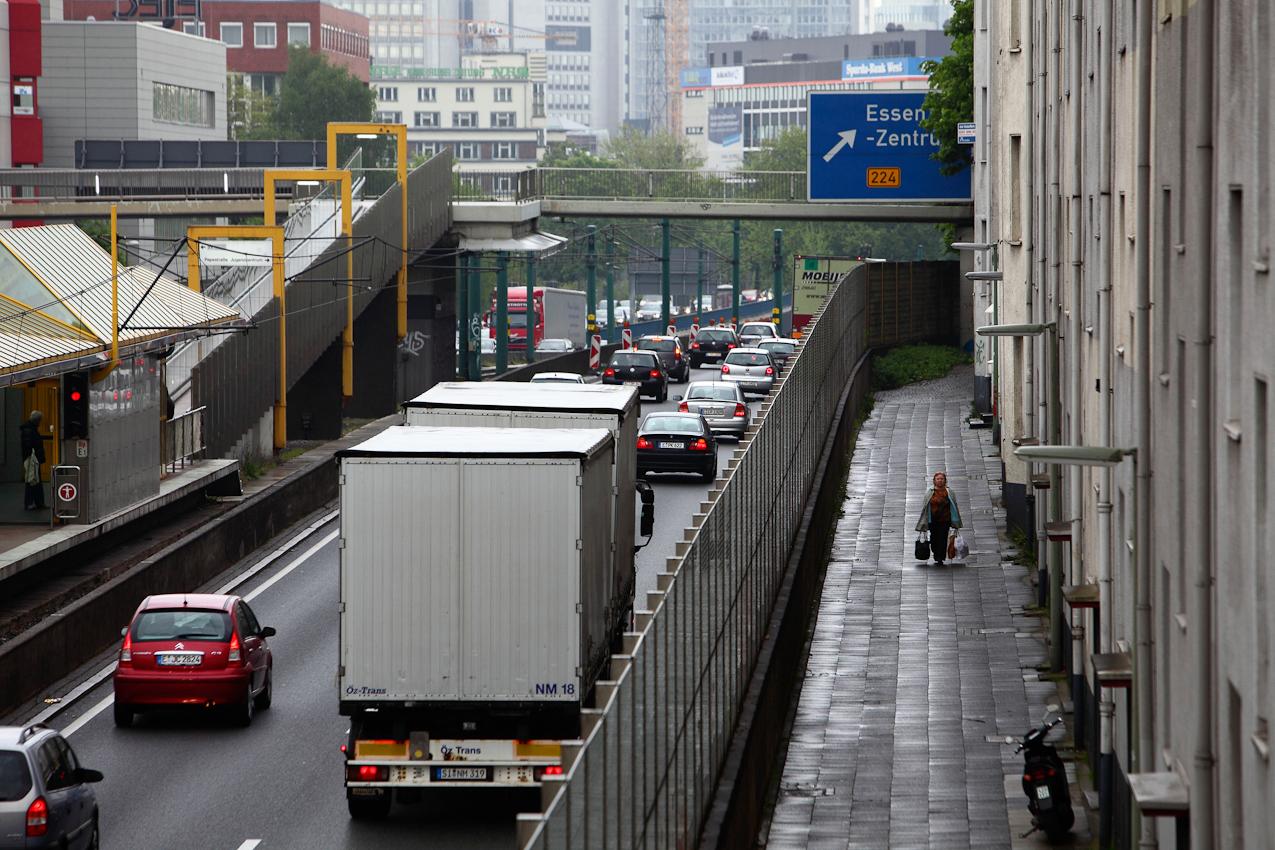 Ein Tag Deutschland, auf der Autobahn A40, Ruhrschnellweg. Fuenf Meter stehen die Wohnhaeuser von der Autobahn entfernt. Zum Laerm der Strasse kommt noch das Rattern der Strassenbahnen auf dem Mittelstreifen. Dafuer kommen die Pendler ohne Stau nach Muelheim. Essen, NRW, Deutschland.