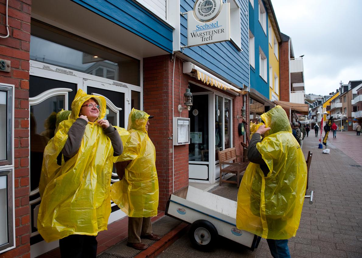 Helgoland, Land & Leute: Eine Touristengruppe bereitet sich in der Haupteinkaufsstrasse Lung Wai auf einen Inselrundgang bei Wind und Regen vor.