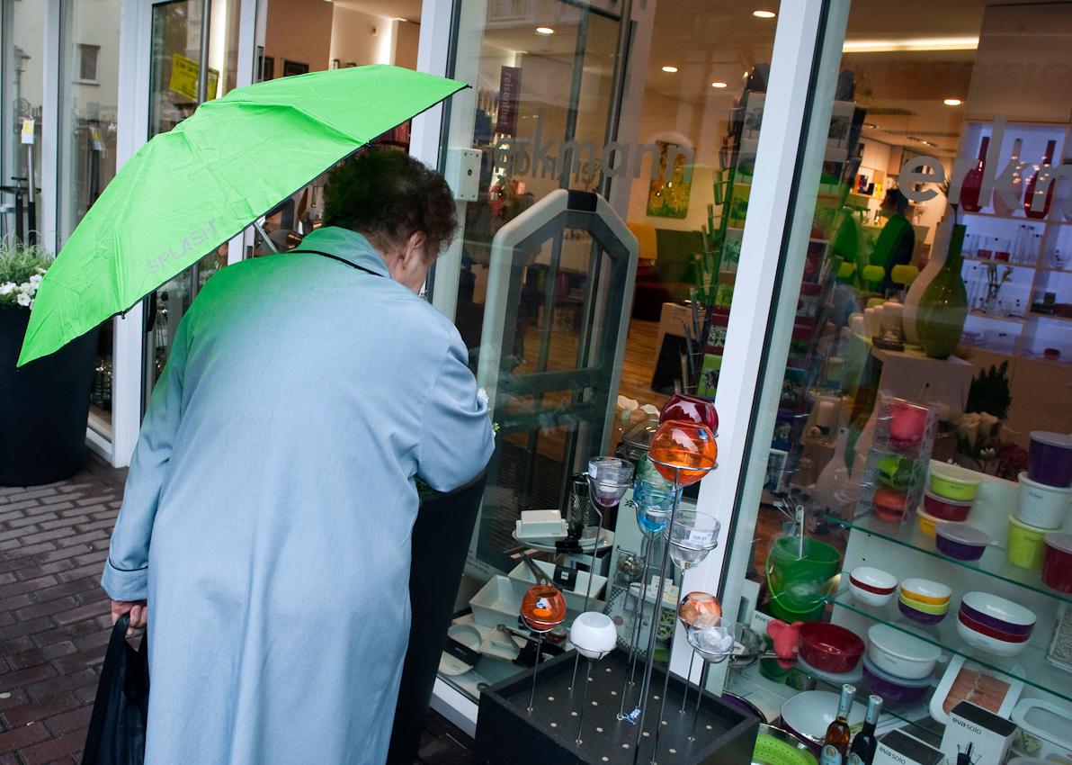 Werne a.d. Lippe, DEU, 07.05.10 - Eine ältere Frau schaut sich am Freitag, 7. Mai 2010, in Werne an der Lippe bei regnerischem Wetter bunte Windlichter vor einem Dekorationsgeschäft an.