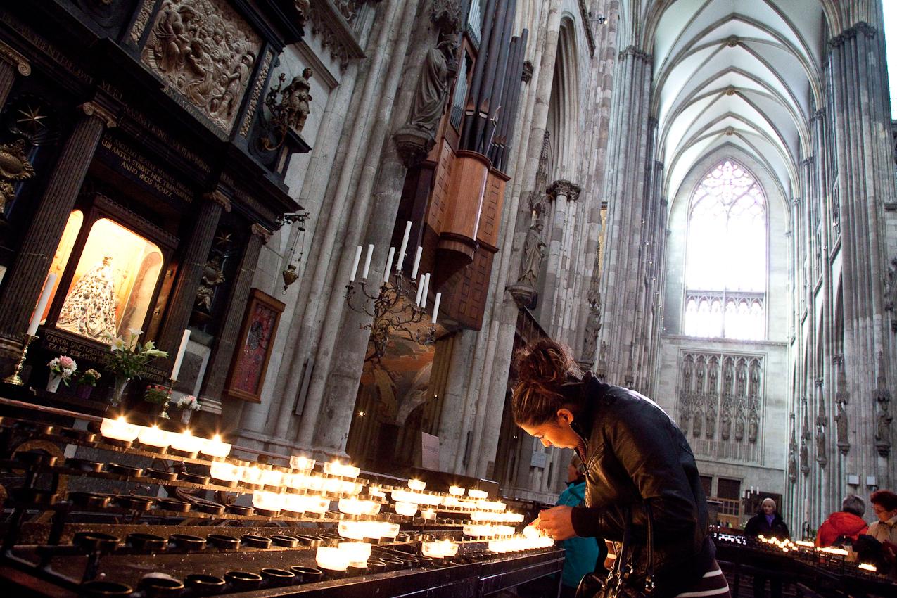 Besucherin zündet vor der Schmuckmadonna eine Kerze an.
