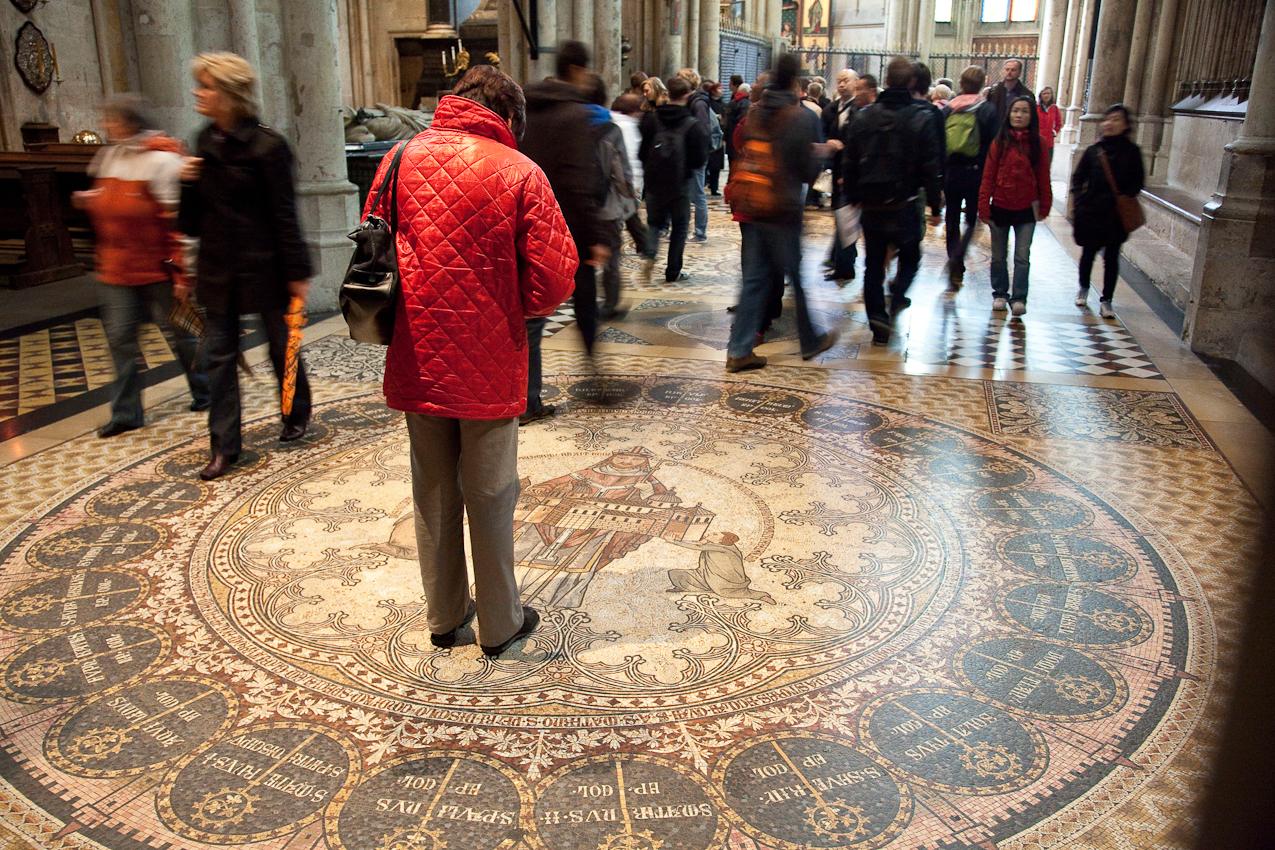 Frau in Rot betrachtet eingehend das Fußbodenmosaik.