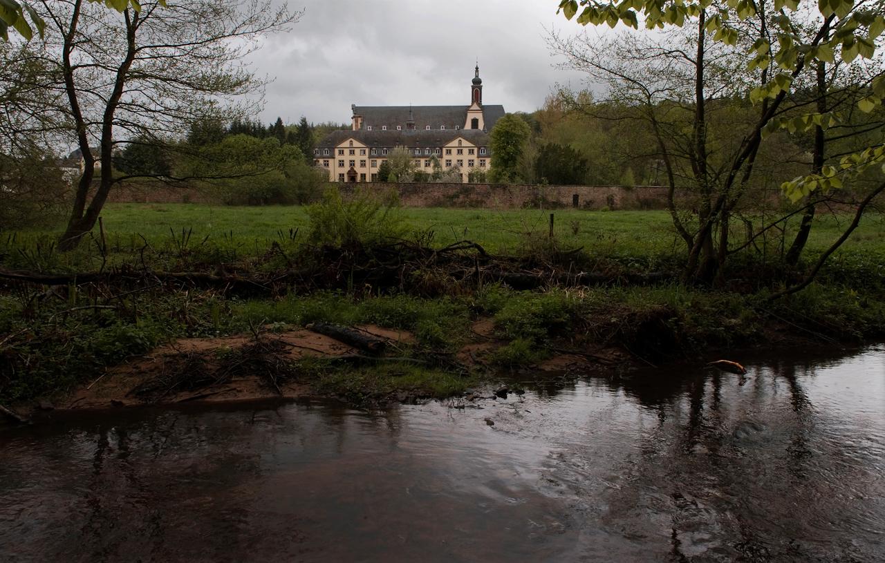 Am Mittag ziehen dunkle Wolken über Kirche und Wohntrakt der Zisterzienser-Abtei Himmerod im Tal des Flüsschens Salm in der Eifel.