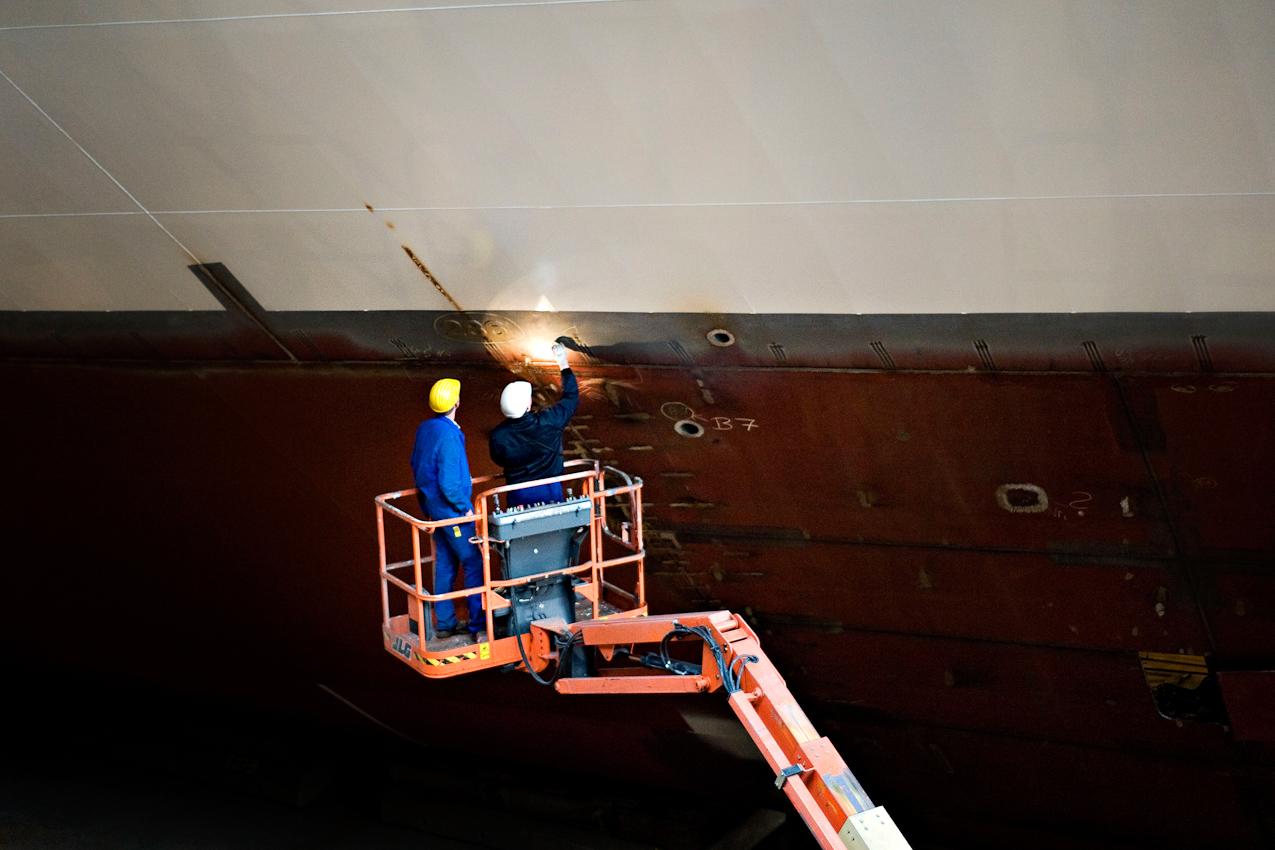 Werftarbeiter kontrollieren eine Schweißnaht an der Außenwand des Rumpfs der AIDAsol.