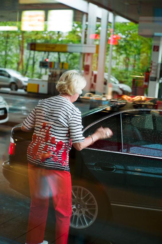 Ein Tag durch Deutschland: im Schnelldurchlauf in 8 Stunden trampenderweise von Hamburg zum Bodensee, entlang der A7 der längsten deutschen Autobahn. hier: eine Reisende steigt an der Tankstelle Riedener Wald in den vorgefahrenen Wagen ein.