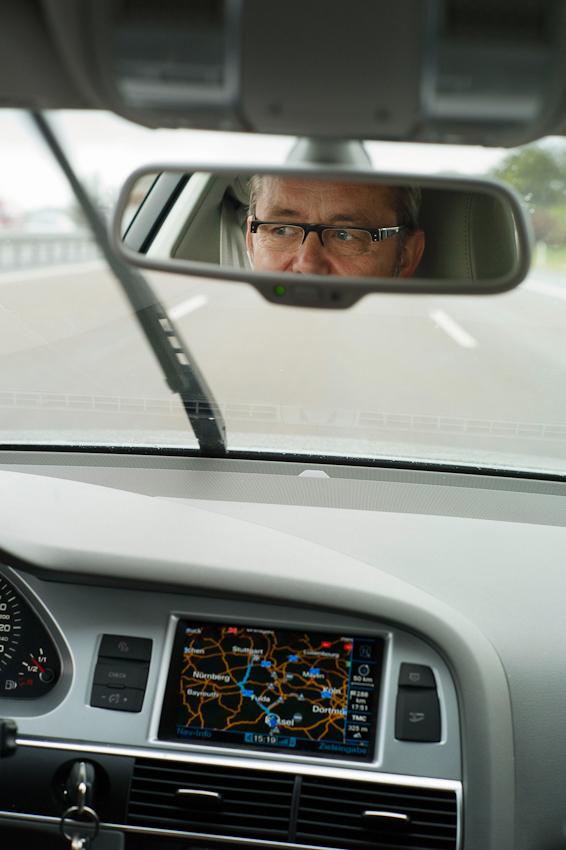 Ein Tag durch Deutschland: im Schnelldurchlauf in 8 Stunden trampenderweise von Hamburg zum Bodensee entlang der A7, der längsten deutschen Autobahn. Herr Klaus Grabbe, Bürgermeister von Neckarsulm, nimmt uns 400 km mit, hier zu sehen im Rückspiegel seines Audis. Er erzählt uns von seinen wilden Zeiten in einer Landkommune  und davon, dass Neckarsulm seit 2002 fünfmal den Spitzenplatz in der Solarbundesliga belegt hat.