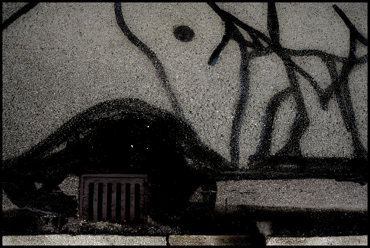 """Serie aus dem Langzeitprojekt """"FLICKWERK"""". Bestandsaufnahme vom 7.Mai 2010. Im Projekt """"FLICKWERK"""" werden Straßenausbesserungen in Hinsicht auf Ihre formale Bildsprache dokumentiert. Bei vielen der dokumentierten Motive fällt auf, dass sich die Ausbesserungen nicht strikt an die Rissbildung in der Teerdecke orientieren. Inwiefern dies von Seiten des Straßenarbeiters bewusst oder unbewusst geschieht bleibt offen.Euroindustriepark, MUNCHEN."""