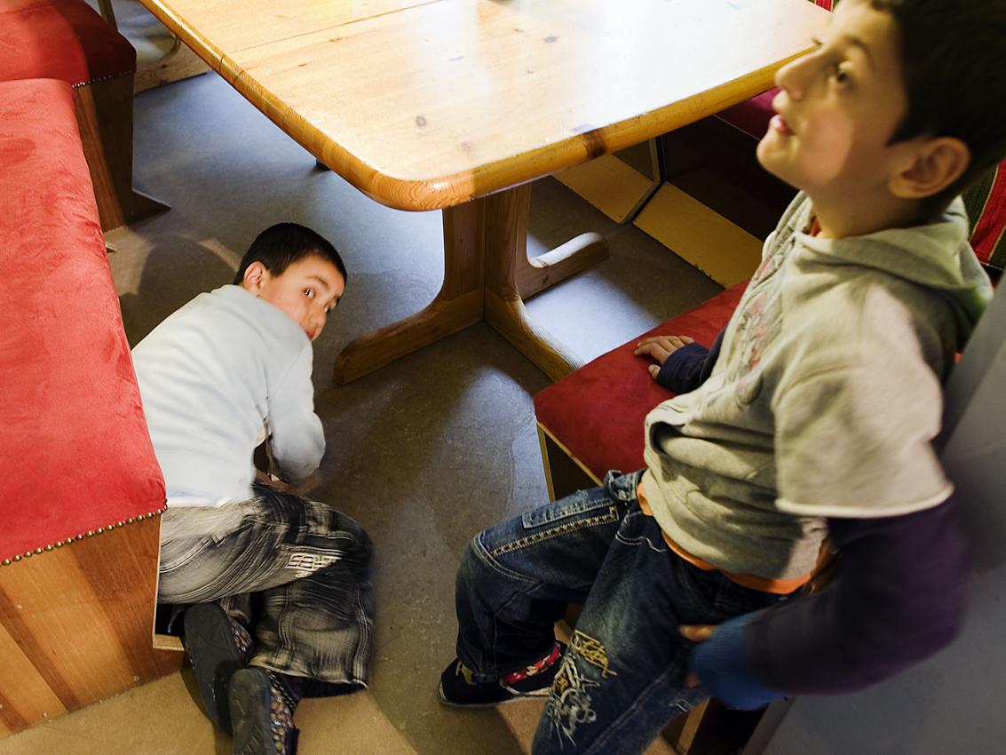 """Leben am und unterm Tisch: Choschnar hat seinen Saft verschüttet und muss aufwischen, währenddessen versucht Walat zusätzliche Zeit am PC auszuhandeln - vergeblich.    Der Hort, Dieselstraße 1, in Herford besteht seit 1989  als sozialpädagogische Tageseinrichtung fur Grundschulkinder. 2007 wurde er im Rahmen der Kampagne """"Deutschland Land der Ideen"""" vom Bundespräsidenten zu einem von 365 """"ausgewählten Orten. Bis 2008 unterlag der Hort dem Gesetz uber ,,Tagesstätten fur Kinder"""" (GTK), im seitdem in Nordrhein-Westfalen geltenden Kinderbildungsgesetzt sind Horte nicht mehr als Regeleinrichtungen erwähnt. Kommunale Sparzwänge bedrohen die Qualitat der Arbeit des vom lokalen Verein fur soziale Arbeit und Beratung getragenen Hortes zusätzlich."""