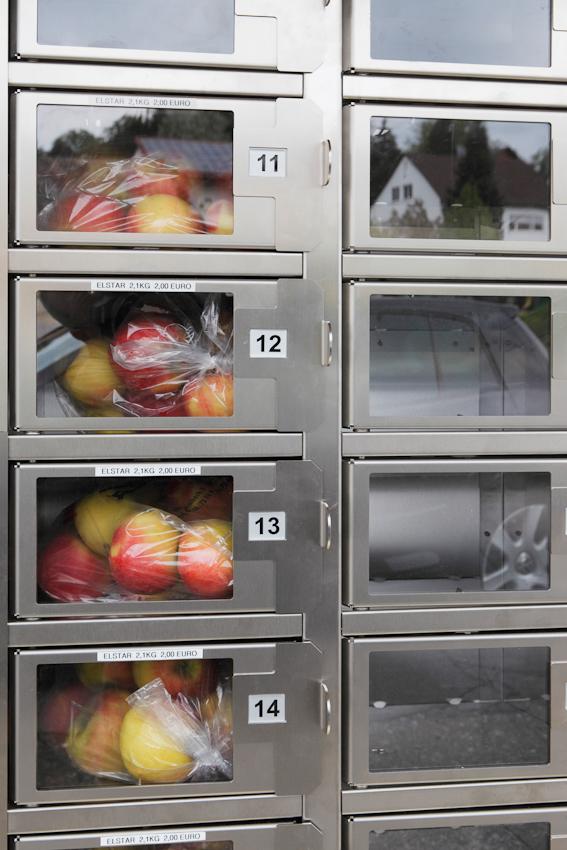 """In der Dorfmitte von Leimbach bei Markdorf steht an der Durchgangsstraße B33 der Apfelautomat des Obsthof Heimgartner. Er ist wohl die kleine und aktuelle Ausgabe der Restaurantversion """"Automat"""" die in den 30er Jahren in den USA während der Depressionszeit beliebt war. Das letzte Automatrestaurant schloss in den USA im Jahre 1991 in New York. So findet eine eine deutsche Erfindung aus dem Jahre 1896 auf Umwegen und in einer Verkleinerung den Weg zurück."""