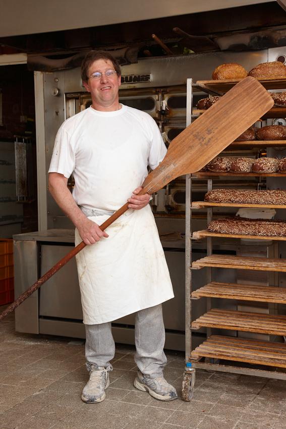 """Bäckermeister Jens Afheldt (47) aus Reinfeld ist seit 2.00 Uhr morgens mit einem Gesellen und einem Lehrling in der Backstube beschäftigt. Mit dem Brotschieber hat er gerade um 7.30 Uhr 35 Brote aus dem Backofen geholt. In seinem Familienbetrieb """"Bäckerei Heinrich Rohlf"""" werden an diesem Freitag 2000 Brötchen in 20 Sorten, 200 Brote in 12 Sorten sowie zahlreiche Kuchen gebacken und in 3 Filialgeschäften verkauft."""