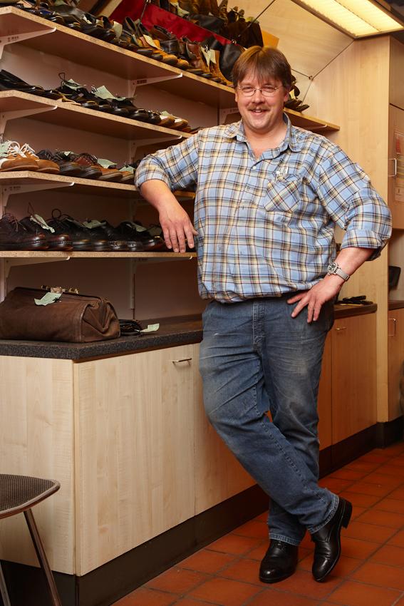 Schuhmachergeselle Thorsten Voß (41) arbeitet in Reinfeld als Angestellter der Firma Herbert Schubring, Inhaber Olaf Schubring, in einem Ladengeschäft in der Raiffeisenpassage. Dieser Freitag beginnt um 7.00 Uhr mit Absatzreparaturen an 12 Paar Schuhen, 3 Paar Sohlenreparaturen und 2 Paar Sohlenbefestigungen. Zwischendurch müssen Kunden bedient werden, das beinhaltet die Annahme von Reparaturen bis zum Verkauf von Schuhcreme. In der Mittagspause ist kurz Zeit fur die Fotos, danach geht es weiter mit Stepparbeiten an Schuhen und Handtaschen, Erneuerung von Fersenfutter, Decksohlen, Klett- und Reißverschlussen und noch einmal 2 Paar Absatzbefestigungen.