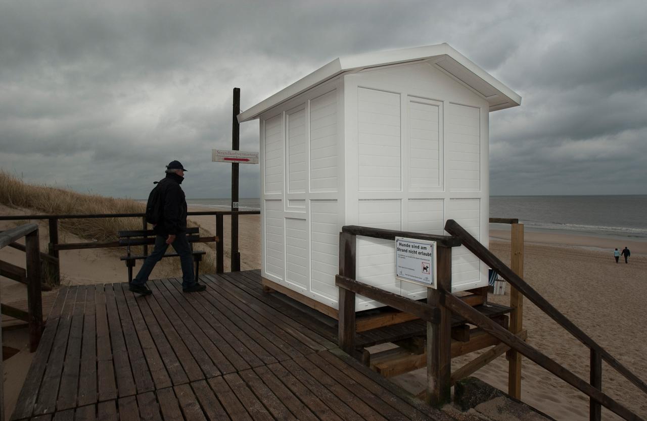 """Am Strandübergang beim Südwaldchen in Westerland auf Sylt pfeift ein hartnackiger Spazierganger: ,,Wir wollen Sonne, keinen Regen, wir wollen ohne ..."""""""