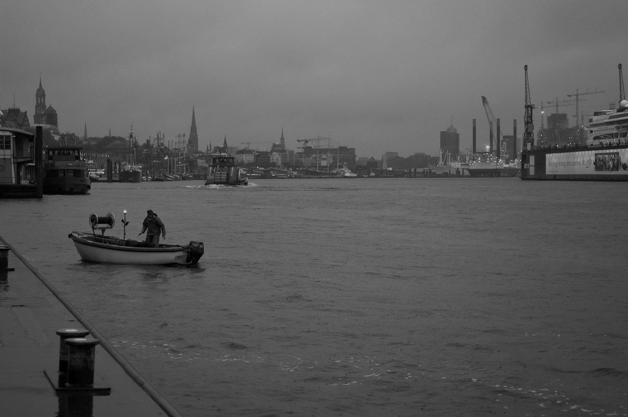 Elbfischer Olaf Jensen fischt mit Aalreusen in der Elbe am St.Pauli Fischmarkt. Jensen fischt im kleinen offenen Boot fahrt er auf Fischfang im Hafenbereich und der Elbe. Dabei kommt er an grossen Containerschiffen, Terminals, und unter der Koehlbrandbruecke sowie zahlreichen Schleusen vorbei.