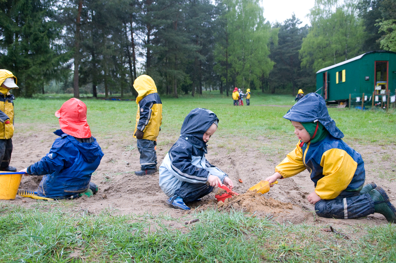 8:43 Uhr. Waldkindergarten Buxtehude. Die Sandkiste ist drei Meter breit und endlos lang: der Waldweg. Außer ein paar Schaufeln und Eimern gibt es kein vorgefertigtes Spielzeug. Sprache ist sehr wichtig. Die Kinder verabreden, ob der Hügel eine Ritterburg ist oder ein Berg, der mit Baggern (also Händen) abgetragen werden muss. Die Kinder können in Rufweite spielen, was nicht unbedingt Sichtweite bedeutet. Räumliche Begrenzungen gibt es nicht. Der Himmel ist nach oben offen. Der Jahreslauf wird buchstäblich hautnah erlebt.