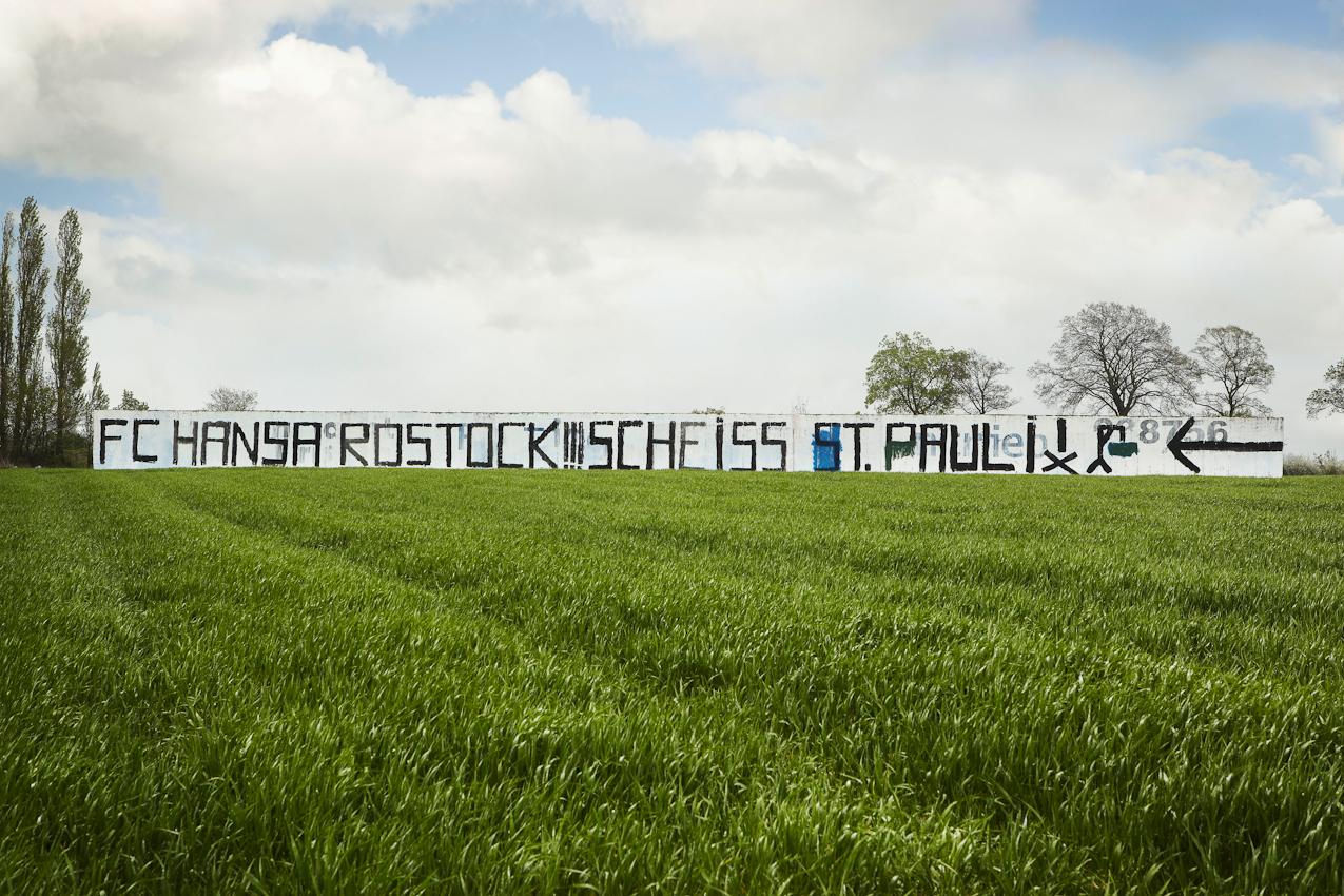 20 Jahre nach dem Mauerfall. FC Hansa Rostock-Fans haben eine Mauer an der A24, Höhe Bobzin bei Wittenburg, Mecklenburg-Vorpommern, bemalt. Das Gelände ist eine landwirtschaftlich genutze Fläche, die Betonmauer ein LPG-Relikt aus DDR-Zeiten. Der FC St. Pauli feiert in diesem Jahr sein 100jähriges Bestehen und wird mit großer Sicherheit in die 1. Bundesliga aufsteigen. Hansa Rostock kämpft hart um seinen Platz in der 2. Liga (Stand 7. Mai 2010). Fußball eint und spaltet die Nation - nicht nur sportlich, sondern auch politisch.