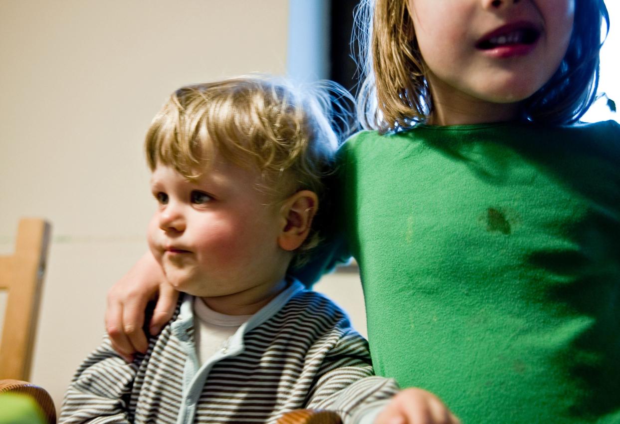 """20.01 Uhr, Küche: Nach dem Abendessen sind Levin und Nia (14 Monate und 5 Jahre) ganz entspannt. Anschließend werden beide Kinder ins Bett gebracht. Das Foto wurde am 07.05.2010 für das Projekt """"Ein Tag Deutschland"""" aufgenommen im Rahmen einer Fotoserie über das Alltagsleben einer Kleinfamilie im Dorf Maintal-Wachenbuchen, 15 Km östlich von Frankfurt am Main. Bei der Serie geht es darum den normalen Alltag eine Kleinfamilie zu zeigen, bei der nach klassischem Rollenmodell vorwiegend die Mutter für die Erziehung der Kinder zuständig ist. Die Mutter arbeitet freiberuflich als Fotografin, der Vater geht einem klassischen Bürojob nach und arbeitet jeden Tag 20 km entfernt. Miteinander, Nebeneinander und Gegeneinander sind das Thema der Serie mit Fokus auf der Beziehung der Geschwister untereinander, die den Familienalltag maßgeblich mitbestimmen. Die Serie über den Familienalltag ist als Langzeitprojekt angelegt. Die Fotos entstanden alle in der Wohnung der Familie, die Dreh- und Angelpunkt des Familienlebens ist. Zur Familie gehören der Vater Thomas Schäfer, die Mutter Meike Fischer (die auch fotografiert hat), die 5-jährige Tochter Nia und der 14 Monate alte Sohn Levin."""