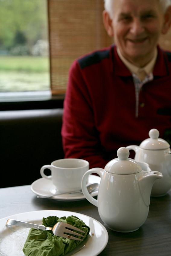 """Am Nachmittag machen Elli und Gert einen Ausflug: Kuchen essen im Cafe """"Emma am See"""" im Burgerpark. Das erste Stück Frankfurter Kranz hat Elli schon aufgegessen, jetzt ist sie noch einmal zur Kuchentheke gegangen. Gert lacht, weil Elli immer ihre Serviette zerknüllt, dabei kann man mit der doch """"dolle Dinge"""" machen. Zum Beispiel etwas daraus falten."""