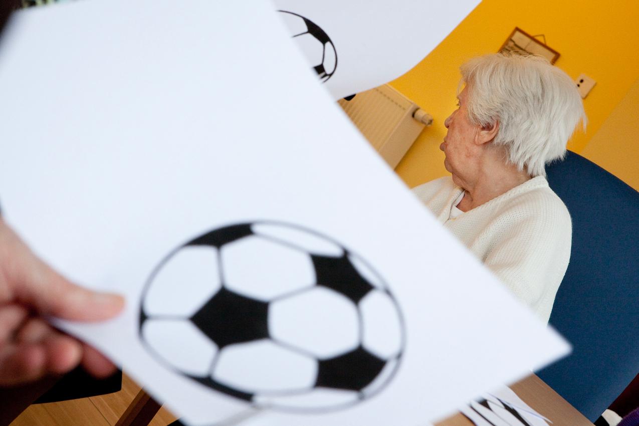"""<p>Anna Lorenzen lebt mit einer Demenz im mittleren Stadium in der """"Tulpe"""", der gerontopsychiatrischen Station des Stadtdomizil in Hamburg. Anlässlich der bevorstehenden Fußball-WM schneiden sie und einige Mitbewohner im Rahmen der Beschäftigungstherapie Papierfußbälle aus, die anschließend an die Fenster geklebt werden sollen.</p>"""