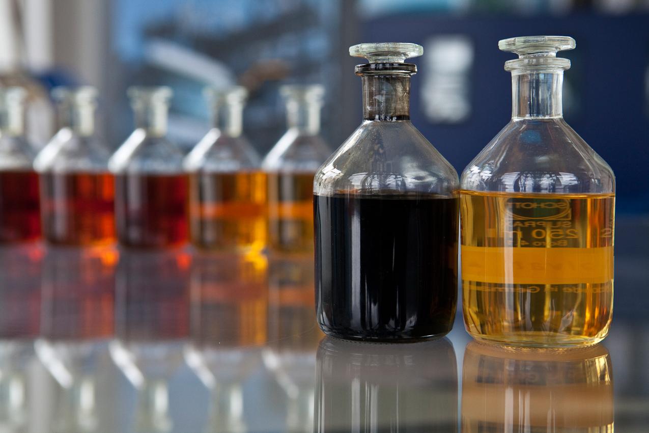 Erst schwarz, dann gold - so sieht der Kontrast zwischen dem Altöl und dem recycelten Produkt aus. Im Hintergrund sind die Ergebnisse der Zwischenschritte des Verfahrens zu sehen.