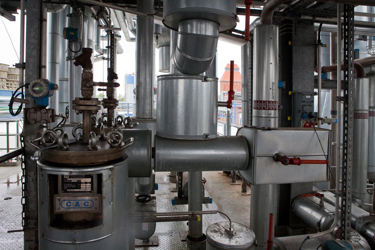 Kurz vor der Fertigstellung durchlauft das Öl diesen Bereich der von der Raffinerie selbst entwickelten Selektiv-Raffination. Das Gebäude im Hintergrund erinnert an die lange Tradition des Standortes. Heute ist er der größte Altölrecyclingstandort Deutschlands.