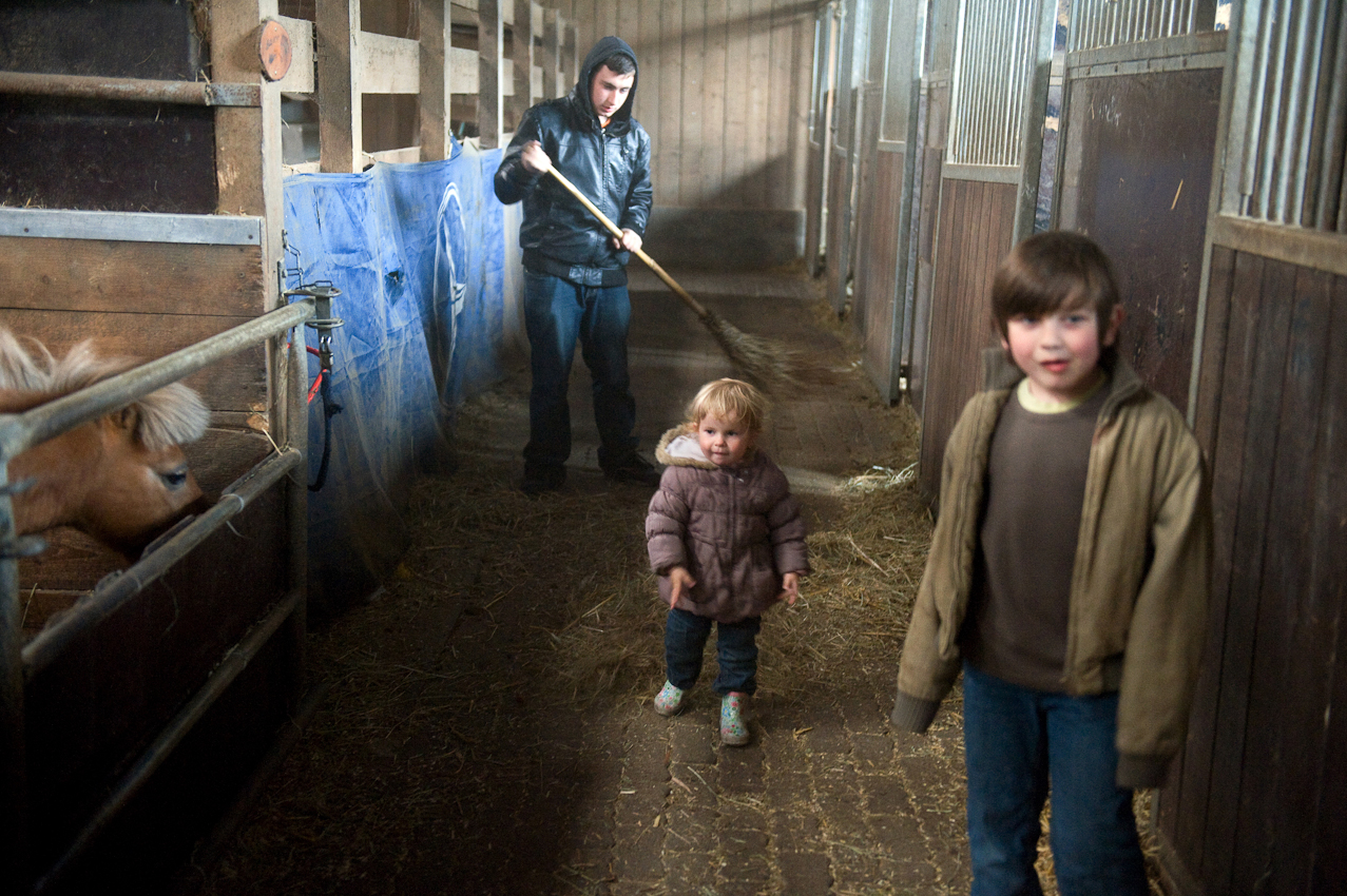 Josefine (2 Jahre) und Yannis (8 Jahre) spielen im Stall, Max (14 Jahre) fegt den Stall. In ihrer Freizeit sind die Kinder gerne im Reitstall, der direkt neben dem Haus der Töpfers angrenzt. Nele (10 Jahre) hat fast täglich Reitunterricht mit ihrem Pferd Askari.