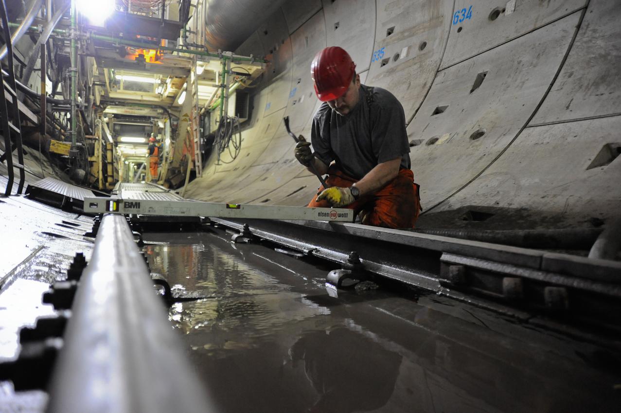 Baustelle der neuen U-Bahnlinie U4 in die Hafencity Hamburg. Mineure bauen mit Hilfe der Schildvortriebsmaschine (V.E.R.A. von der Elbe Richtung Alster) den 682. Tubbingring im Inga-Tunnel II ein. Schichtbeginn 5:30 Uhr im Startschacht Hafencity. Ein Tunnelbauer prüft ob die Schienen fur die Materialbahn in der Waage sind.