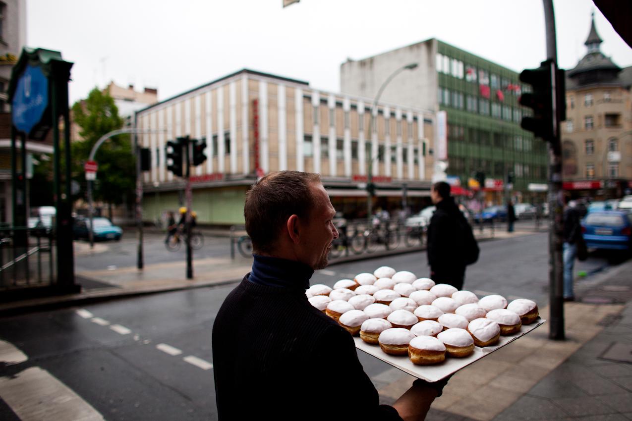 Ein Mann traegt ein Blech mit suessem Gebaeck, sogenannten Berlinern, von seinem Lieferwagen in ein Backwarengeschaeft in der Karl-Marx-Strasse im Berliner Stadtteil Neukoelln.