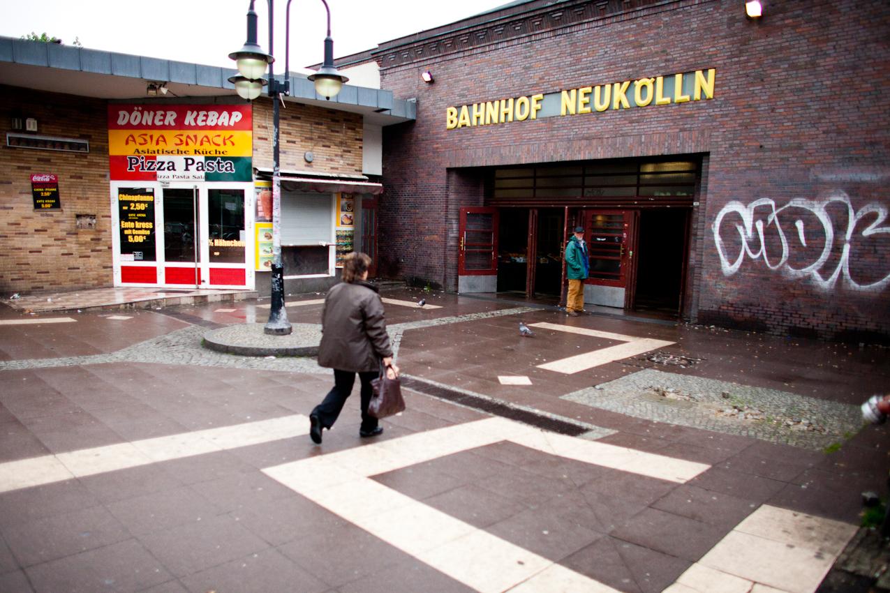 Eine Frau passiert die Hinweisschilder zu einer Pizzaria, Asia Snack und Kebab Doener vor dem S-Bahnhof in der Karl-Marx-Strasse im Berliner Stadtteil Neukoelln.