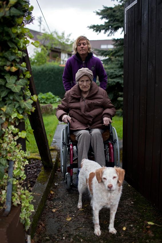 Ausflug: Enkeltochter Rita Lohmann schiebt ihre Oma durch den Garten, Hund Mirza weicht nicht von der Seite.