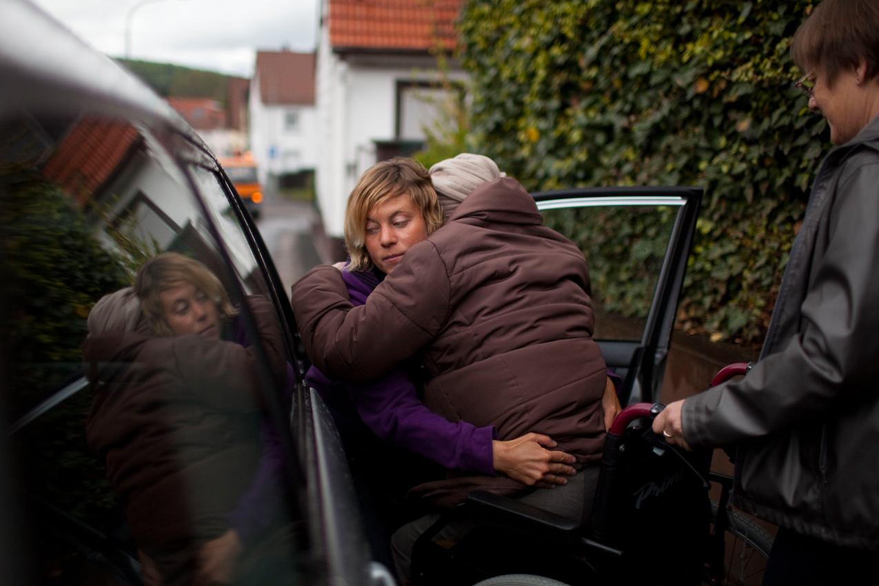 """Arztbesuch: Mutter und Tochter helfen Elfriede Buch ins Auto. Ein Arztbesuch steht auf dem Programm. Vor einer Woche stürzte Frau Buch und brach sich eine Rippe: ,,Es geht schon, es tut nicht so weh."""" Wie auch schon ihr ganzes Leben lang, ist Frau Buch hart im Nehmen und beklagt sich kaum."""